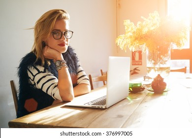 Portrait of attractive smiling female student posing while resting after work on her portable laptop computer during coffee break. flare light