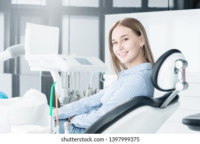Portrait of an attractive smiling girl blonde in a dental chair. Happy customer dental cabinet