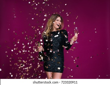 Portrait of attractive smiling girl with tinsel confetti in hands bottle of champange and wineglasses with champagne. New year's feeling. Merry christmas