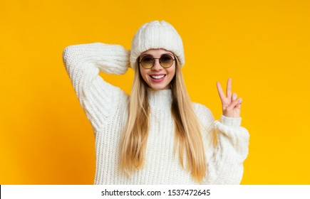 Portrait of attractive smiling girl in white knitted winter set and sunglasses over yellow background, showing victory sign