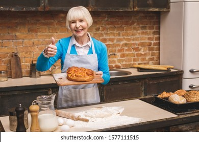 Portrait of attractive smiling happy senior aged woman is cooking on kitchen. Grandmother making tasty baking. Thumbs up.