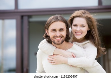 Portrait of attractive smiling married couple outdoors, looking at camera. Close up head shot young positive husband and wife piggyback ride. Happy family and real estate owners or relocation concept