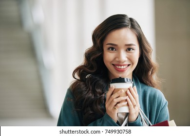 Portrait of attractive smiling Vietnamese woman with take-out coffee