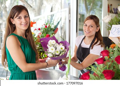 Portrait of an attractive and smiling woman customer client buying a bouquet of white fresh flowers from a fresh flower market stall store and a young shop assistant. Outdoors business shopping.