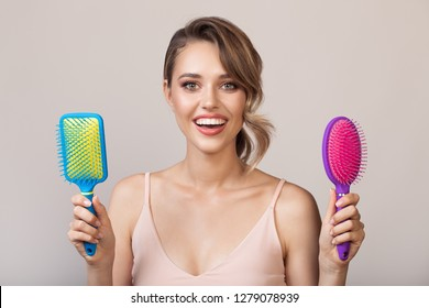 Portrait of attractive smiling woman holding hairbrushes in her hands.