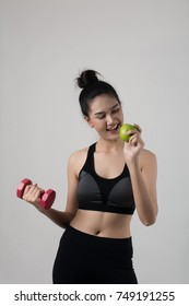 Portrait of attractive smiling woman holding with apple and dumbbells isolated on white background.