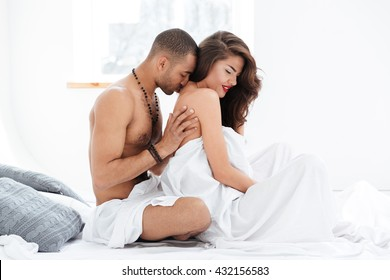 Portrait of an attractive smiling young couple caressing laying in bed together