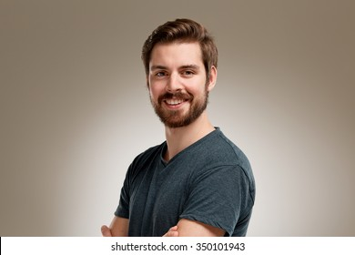 Portrait of attractive smiling young man with beard with crossed arms