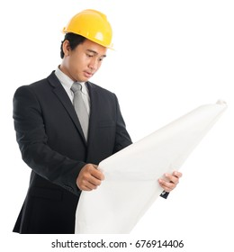 Portrait of attractive Southeast Asian engineer with yellow hard hat reading on blue prints, standing isolated on white background.