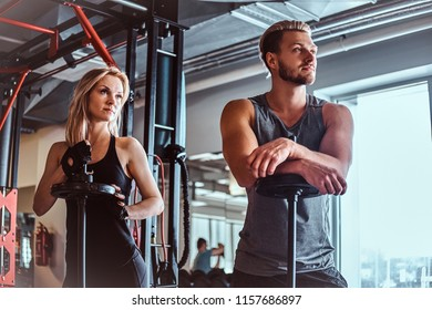 Portrait of an attractive sportive couple posing while leaning on barbells, looking away in a fitness club or gym.