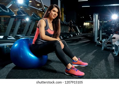 Portrait of attractive sporty woman in gym with fitball