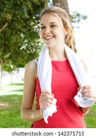 Portrait of an attractive sporty young woman standing in a city park with a towel around her neck, taking a break from exercising during a sunny day.