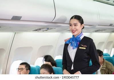 Portrait of attractive stewardess in uniform standing and smile in the economy class of airplane. Passengers sitting on the flight for travel. Transportation and service concept.