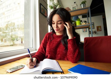 Portrait of attractive student looking at camera while writing down text information in notepad. young creative hipster girl writing impression review of visiting coffee shop in notebook.