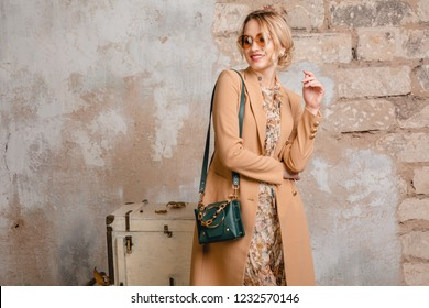 portrait of attractive stylish blonde woman in beige coat walking in street against vintage wall, autumn fashion trend, wearing dress, handbag, sunglasses, urban style