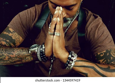 Portrait of an attractive stylish man with a beard and tattoos holding hands like in a prayer together with different jewelries