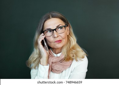 Portrait of attractive successful mature businesswoman wearing stylish accessories biting her lips in doubt and indecisiveness, feeling suspicious whilehaving phone conversation at blank office wall