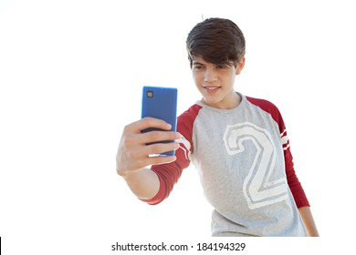 Portrait of an attractive teenager boy holding his smartphone with his hand and taking a selfie of himself against a sunny sky. Using smart phone technology outdoors to take photos.