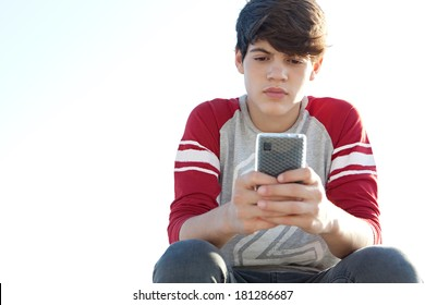Portrait of an attractive teenager boy relaxing and sitting down, holding and using a smartphone for networking during a sunny day with a thoughtful expression, outdoors.