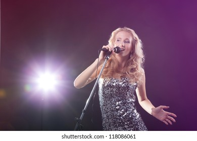 Portrait of an attractive teenager girl  singing with microphone.