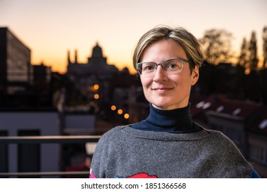 Portrait of an attractive thirty year old white woman posing on a terrace with a colorful sunset background