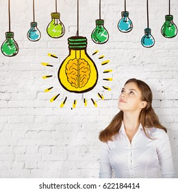Portrait of attractive thoughtful european woman on brick background with drawn light bulbs. Idea concept