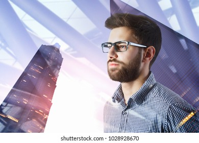 Portrait of attractive thoughtful young european businessman standing on abstract city background with copy space and sunlight. Success and tomorrow concept. Double exposure