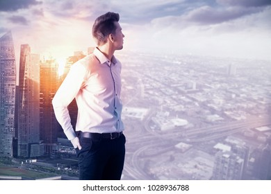Portrait of attractive thoughtful young european businessman standing on abstract city background with copy space and sunlight. Success and employment concept