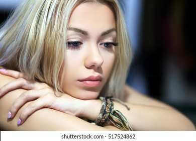 Portrait of attractive thoughtful young woman sitting at home