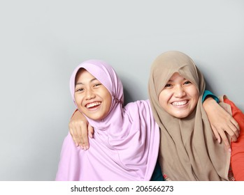 portrait of attractive two young muslim kid having fun together on grey background
