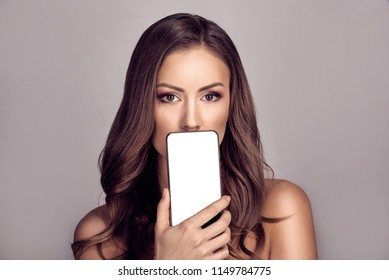 Portrait of attractive woman covering mouth with modern smartphone