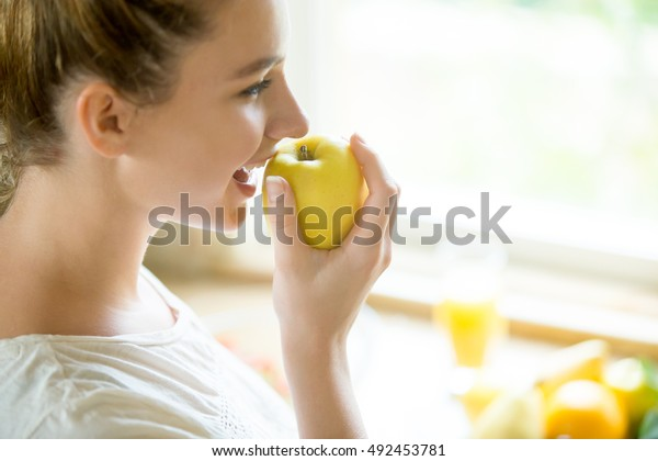 Portrait of an attractive woman eating an apple, her mouth open. Concept photo