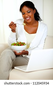 Portrait of an attractive woman eating healthy salad while is sitting on couch in front of her laptop