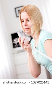 The portrait of an attractive woman heals herself with an inhaler.