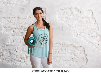 Portrait of attractive woman holding green yoga or fitness mat after working out at home or in club. Friendly smiling sport instructor looking at camera. Healthy life concept