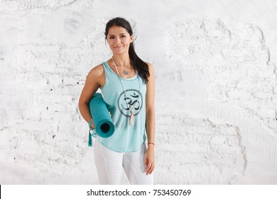 Portrait of attractive woman holding green yoga or fitness mat after working out at home or in club. Friendly smiling sport instructor looking at camera. Healthy life concept. horizontal shot