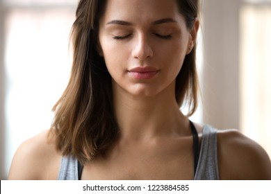 Portrait of attractive woman meditating with eyes closed, female doing restorative yoga exercise, lady relaxing after training at home or studio, stress relief breathing technique. Well-being concept