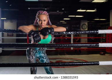 Portrait of an attractive woman with perfect fit body. Female boxer with colored braids posing inside a boxing ring.