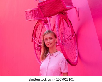 Portrait of an attractive woman in a pink dress on a pink alley, a pink bicycle hangs on the wall.