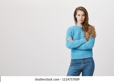 Portrait of attractive woman with poker face standing with crossed hands and being in bad mood, staring with dibelief over gray background. You have not called weeks and now pretend nothing happened