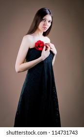 Portrait of attractive woman with a red flower on dress
