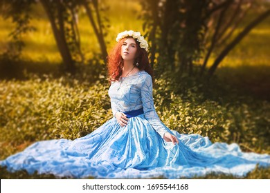 Portrait of an attractive woman with a rim of white flowers and in a blue magnificent dress sitting on the grass in the park against the background of lilac bushes.