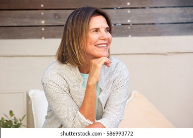 Portrait of attractive woman sitting outside and smiling