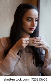 Portrait of attractive woman sitting in a room and drinking tea from cup