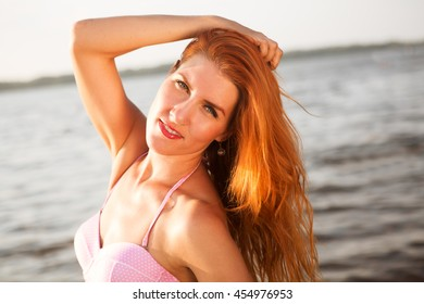 Portrait of attractive woman standing at beach. Happy smiling girl looking at camera