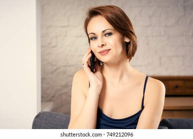 Portrait of attractive woman talking on phone sitting on couch