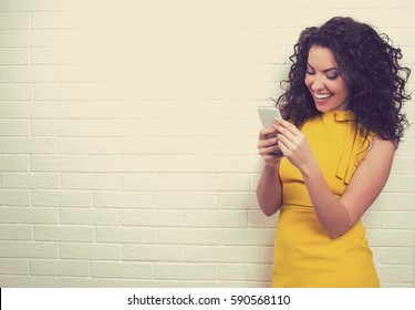 Portrait of attractive woman using high-speed Internet connection, texting her friends via social networks on smart phone isolated against brick wall