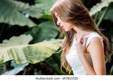 portrait of attractive woman in white dress posing in tropical park