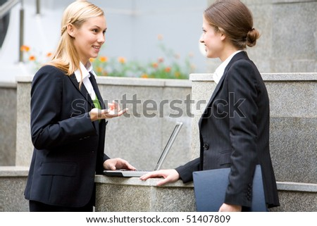 Portrait of attractive women discussing about work near building