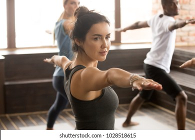 Portrait of attractive yogi girl and a group of young sporty people practicing yoga lesson, standing in Warrior two exercise, Virabhadrasana 2 pose, working out, indoor close up, studio